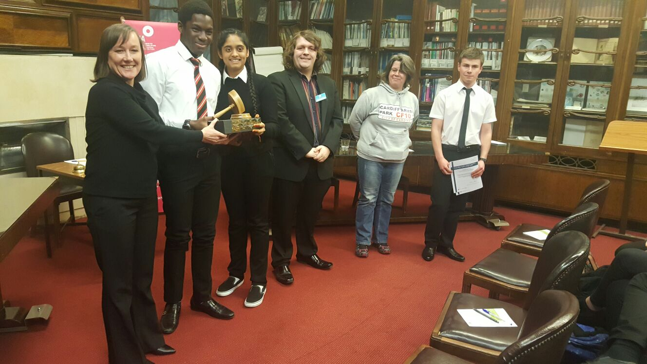 Cardiff Sixth Form College students receive a trophy from Jo Stevens MP, after winning the Wales Schools Debating Championships Grand Finals